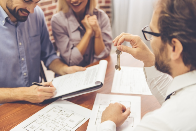 blog image of couple signing papers and receiving keys; blog title: Why Rent Through a Property Management Company